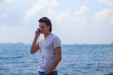 Young man talking by phone on background of the Bosphorus Strait