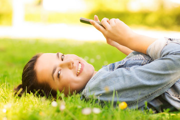 smiling young girl lying on grass