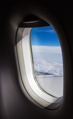 Plane window with blue sky and clouds outside.