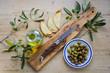Oliven und Ölivenöl arrangiert auf einem Holztisch