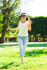 smiling young woman with sunglasses in park