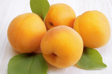 Apricots with leaves on a wooden white table closeup