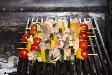 cooking skewers of seafood in a restaurant