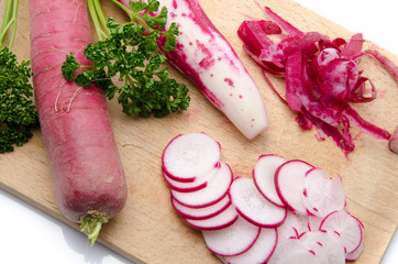 Whole and sliced red radish on a wooden cutting board