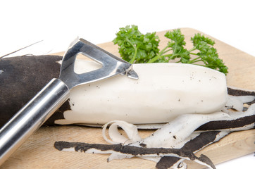 Black radish, parsley and a peeler on a wooden cutting board