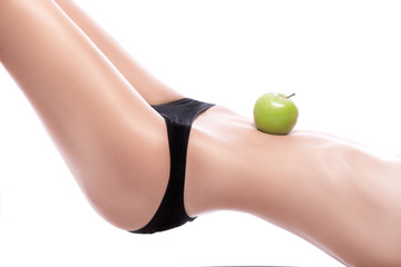 woman holding a green apple on her belly