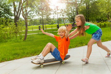 Girl pushes boy with arms apart on skateboard