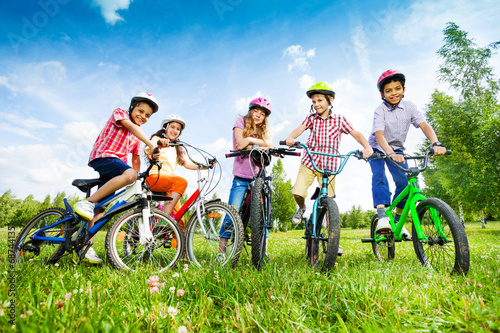 Children in colorful helmets hold their bikes - 68744135
