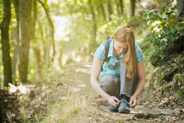 Hiker Tying Her Shoe on a Trail