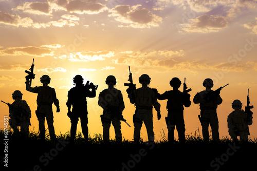 Leinwandbild Motiv silhouette of  Soldiers team with sunrise background