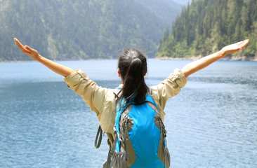 cheering woman tourist open arms to beautiful landscape