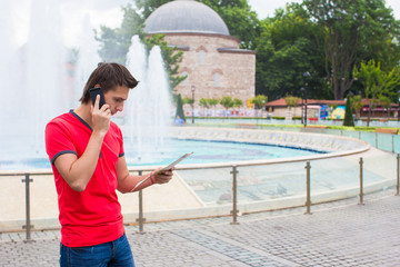 Young businessman using telephone with map in the city