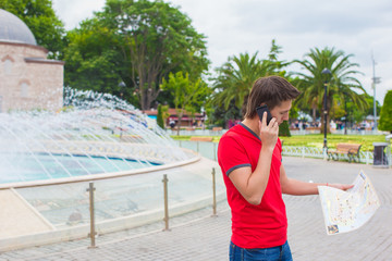 Young man using telephone with map in hands