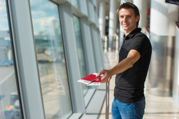 Man holding passports and boarding pass at airport waiting the