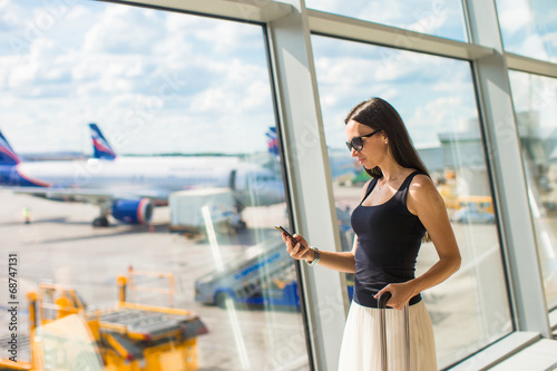 Young woman writing message on phone while waiting for flight - 68747131