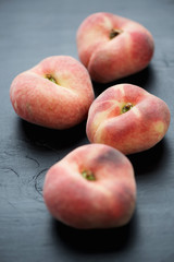 Close-up of ripe saturn peaches over black wooden background