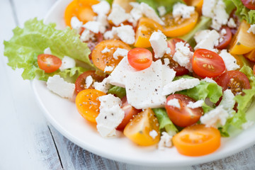 Salad with various types of tomatoes and feta cheese, close-up