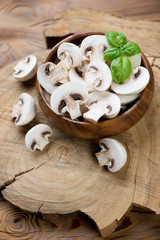 Fresh sliced champignons and green basil over wooden background