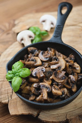 Frying pan with roasted champignons, vertical shot, close-up