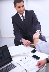 Business people handshake, sitting in the office