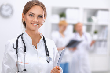 Woman doctor standing with folder at hospital