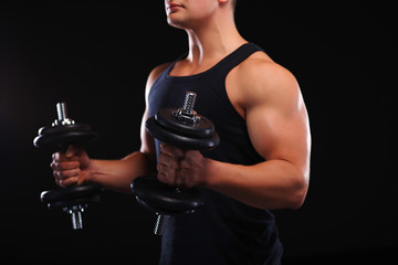 Fit muscular man exercising with dumbbell