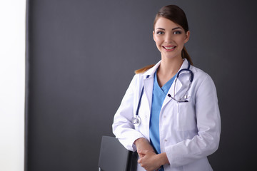 Beautiful female doctor standing near stool isolated grey