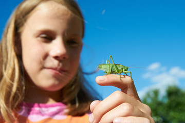Girl with a grasshopper on a hand