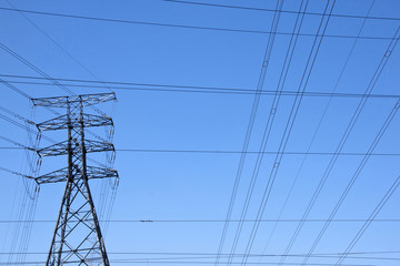 Electricity Pylon With Power Cables Against Blue Sky