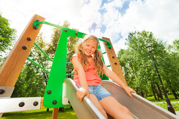 Funny girl on children chute ready to slide