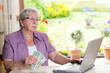 female senior with money is using computer