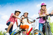 Laughing kids in helmets hold bike handle-bars