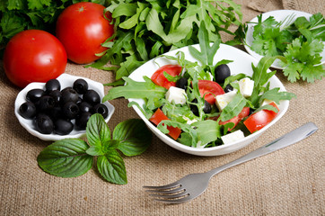 Greek salad in white salad bowl with cutlery and vegetables on s