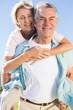 Happy senior man giving his partner a piggy back - 68752161