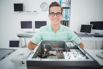 Smiling technician working on broken computer