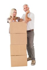 Happy couple leaning on pile of moving boxes