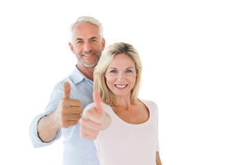 Smiling couple showing thumbs up together