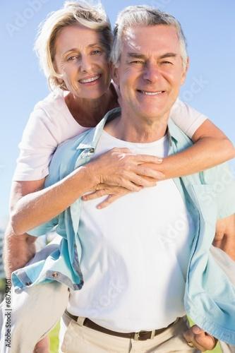 Fotobehang Water Motorsp. Happy senior man giving his partner a piggy back