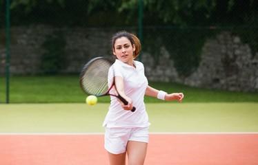 Young tennis player hitting ball