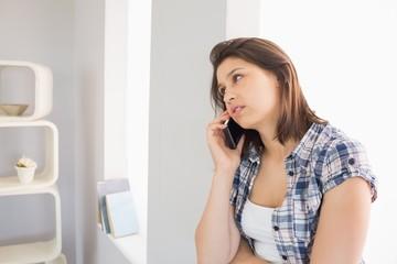Pretty brunette sitting beside her window talking on phone