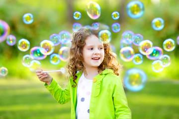A little girl blowing soap bubbles, spring portrait beautiful cu