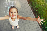 cheerful little girl playing hopscotch on playground