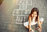 beautiful cheerful little girl playing hopscotch on playground - 68752758