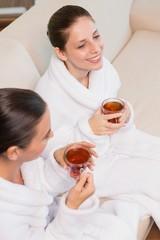 Smiling women in bathrobes having tea