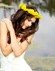 young woman with wreath of dandelions summer outdoor, beautiful