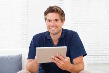 Man Using Digital Tablet On Sofa At Home