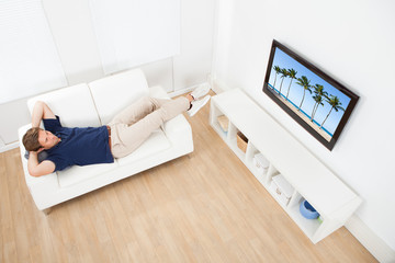 Man Watching Beach View On TV At Home