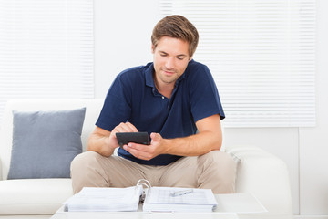 Man Calculating Home Finances At Table