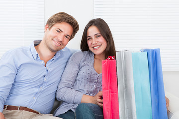 Smiling Couple With Shopping Bags Sitting On Sofa