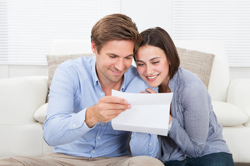 Couple Reading Letter At Home